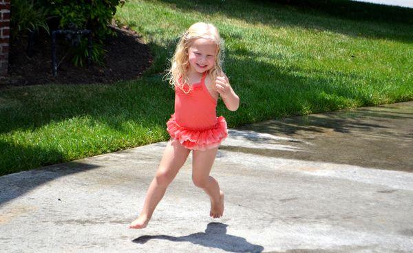 Avery running in sprinkler