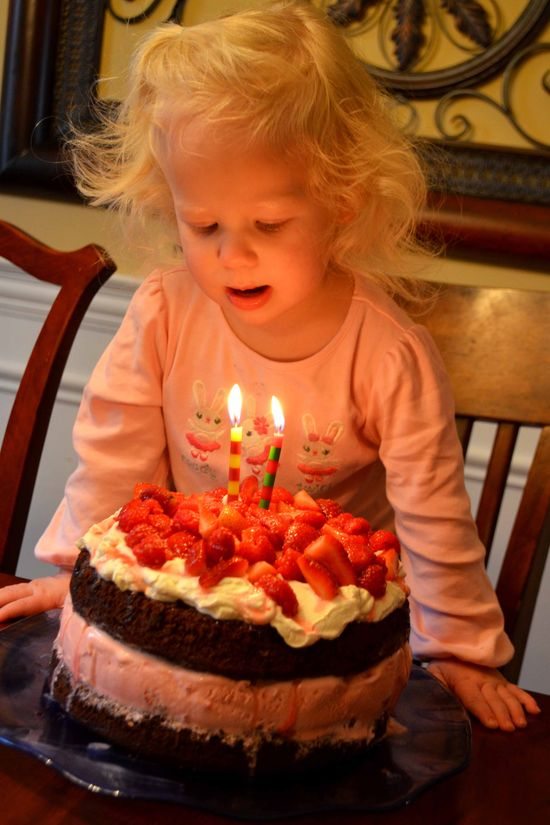 A2 blowing candles on cake